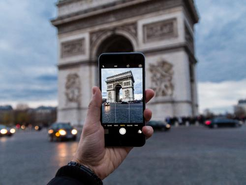 student taking photo of Arc de Triomphe